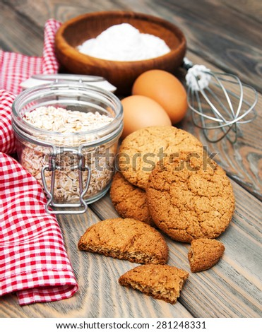 Oatmeal cookies and ingredients on a old wooden background - stock photo