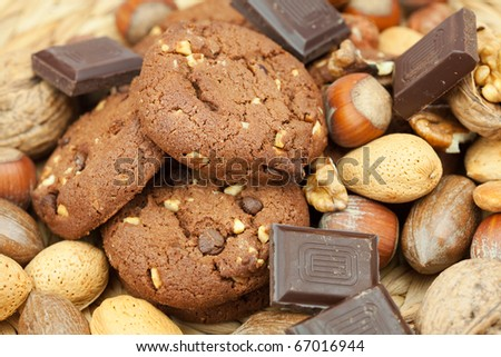 oatmeal cookies, chocolate and nuts on a wicker mat - stock photo