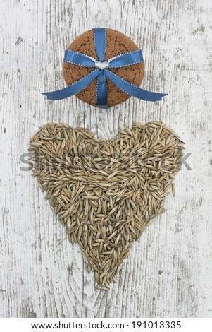 Oatmeal cookies decorated with blue ribbon in the composition with heart shape by oats corn on a old white wooden texture - stock photo