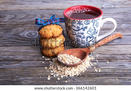 Oatmeal cookies tasty breakfast, cereal in spoon and cacao drink on a wooden background - stock photo