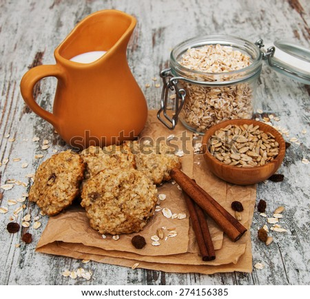 Oatmeal cookies with milk on a old wooden table - stock photo