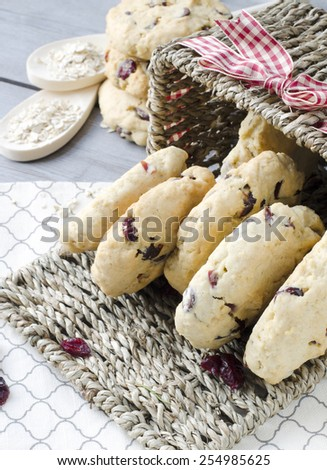 Oatmeal cranberry cookies on a wooden surface with dried cranberries in a basket. - stock photo