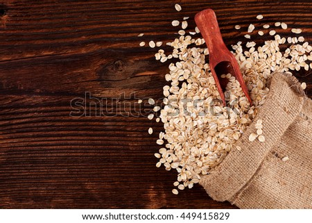 Oatmeal flakes in burlap sack with spoon on brown wooden table, top view.