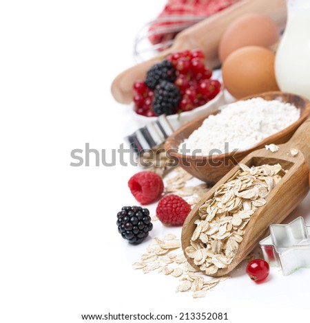 oatmeal, flour, eggs and berries - the ingredients for baking, close-up, isolated on white - stock photo