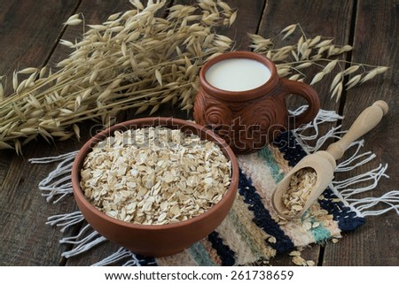 Oatmeal in a clay bowl and a wooden scoop, milk mug, stalks of oats on the background of wooden planks. Selective focus  - stock photo