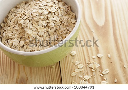 Oatmeal in a green bowl on a wooden table - stock photo