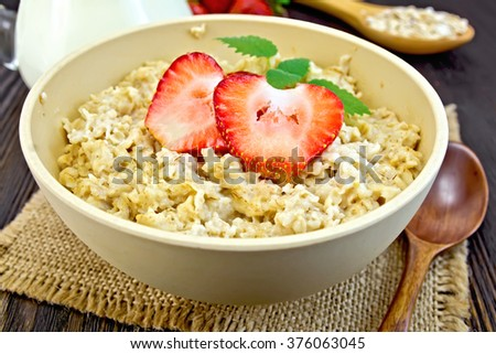 Oatmeal in a yellow cup with strawberries on a napkin of burlap, spoon, milk in a glass jar on the background of dark board