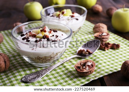 Oatmeal in bowls, yogurt, apples and walnuts on napkin on brown wooden background - stock photo