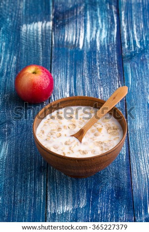 oatmeal in brown bowl with ripe red apple on blue wooden retro background - stock photo