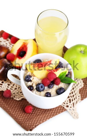 Oatmeal in cup with berries on napkins isolated on white