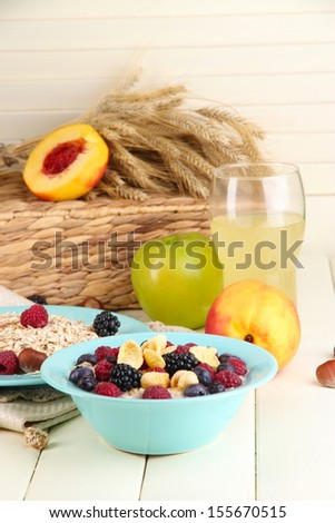 Oatmeal in plates with berries on napkins on wooden table on bright background