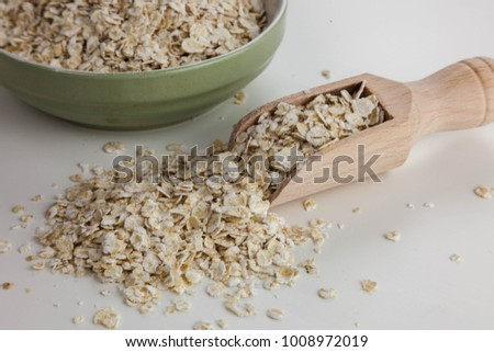 Oatmeal in the wooden spoon isolated on the white background