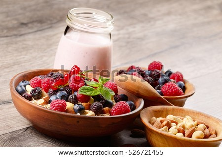 Oatmeal oats with berries nuts and yogurt on the wooden table