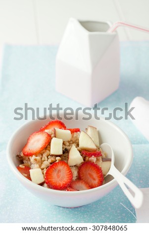 oatmeal or porridge with strawberries, apples and nuts in white bowl - stock photo