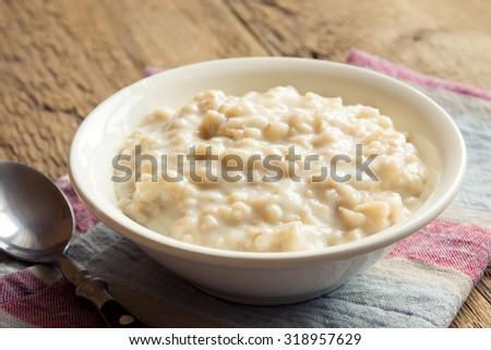 Oatmeal porridge in bowl for breakfast on rustic wooden table - stock photo