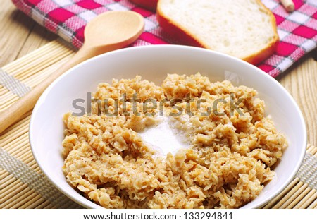 Oatmeal porridge in bowl with butter