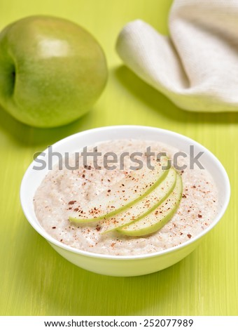 Oatmeal porridge with apple slices and cinnamon in white bowl - stock photo