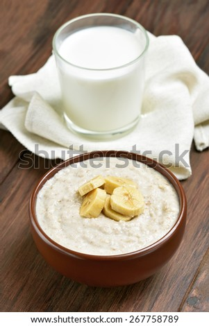 Oatmeal porridge with banana slices and glass of milk  - stock photo