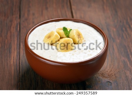 Oatmeal porridge with bananas slices in ceramic bowl on wooden table, close up view - stock photo
