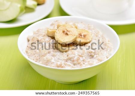 Oatmeal porridge with bananas slices in white bowl on green table - stock photo