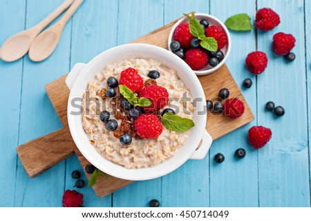 Oatmeal porridge with fresh raspberry and blueberry on bright blue background. Healthy breakfast for children and parents. Tasty vegetarian food. - stock photo