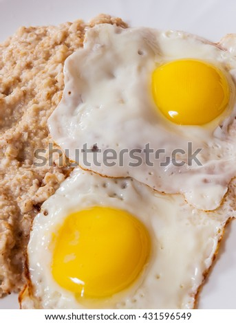 oatmeal porridge with fried egg in a plate on wooden table