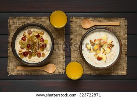 Oatmeal porridge with grapes, apples and walnuts in rustic bowls, glass of juice and wooden spoon on the side, photographed overhead on dark wood with natural light - stock photo