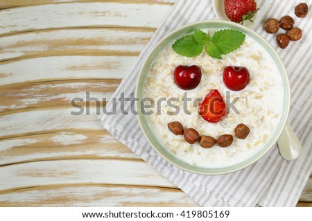 oatmeal porridge with milk and  berries- healthy, funny breakfast  - stock photo