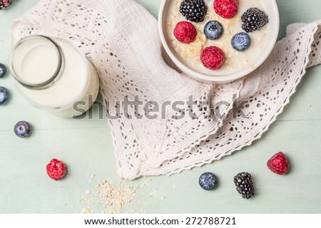 oatmeal porridge with milk and berries on kitchen towel, top view - stock photo