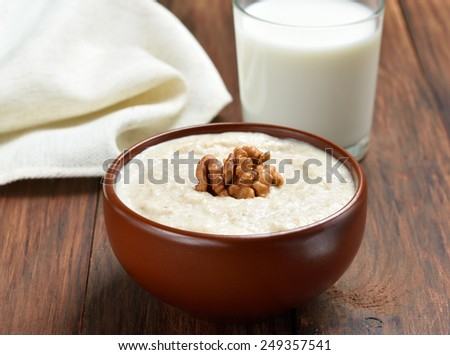 Oatmeal porridge with walnuts and glass of milk on wooden table, close up view - stock photo