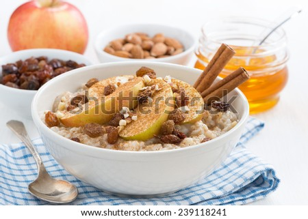 oatmeal with apples, raisins and cinnamon for breakfast on white table, close-up, horizontal - stock photo