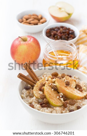 oatmeal with apples, raisins, cinnamon and ingredients on white wooden background, vertical