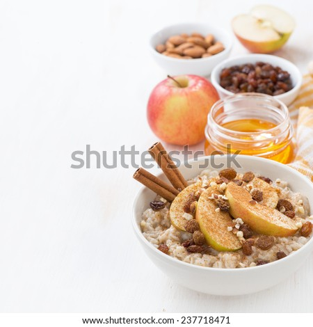 oatmeal with apples, raisins, cinnamon and ingredients on white wooden table, close-up - stock photo