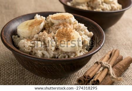 Oatmeal with banana and cinnamon in the bowl and cinnamon sticks on sackcloth - stock photo