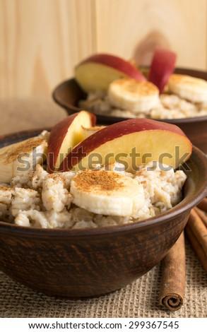 Oatmeal with banana, apple and cinnamon in the bowl and cinnamon sticks on sackcloth - stock photo