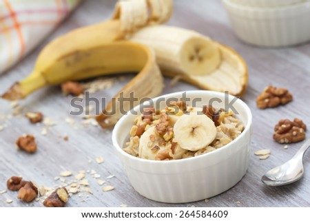 Oatmeal with banana, honey and walnuts for breakfast  - stock photo