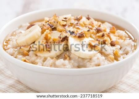 oatmeal with banana, honey and walnuts in bowl, close-up, horizontal - stock photo