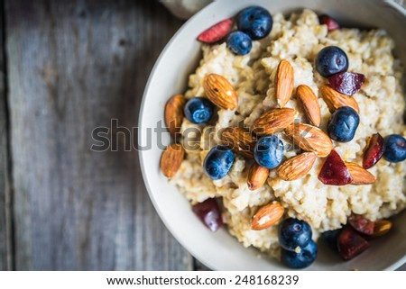 Oatmeal with berries and nuts - stock photo