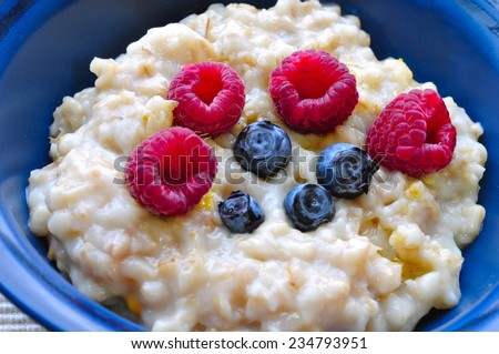 oatmeal with berries in a blue bowl - stock photo