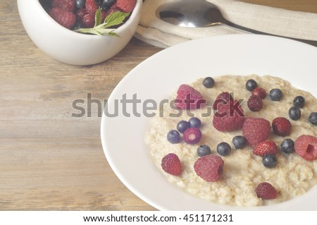 Oatmeal with  berries (raspberry, wild strawberry, blueberry) in white plate on wooden background. Retro toned image