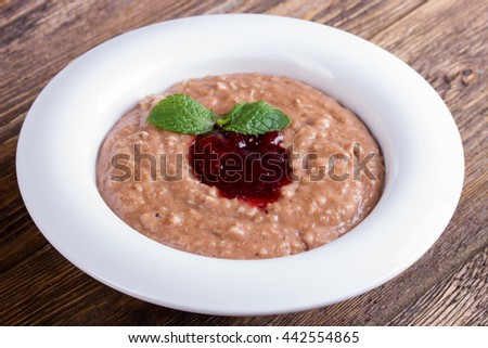 Oatmeal with chocolate, jam and mint leaves
