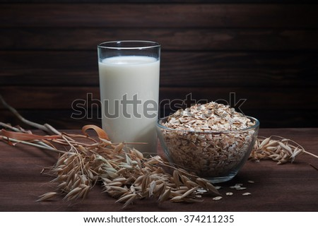 oatmeal with ears of oats and a glass of milk on wooden dark background