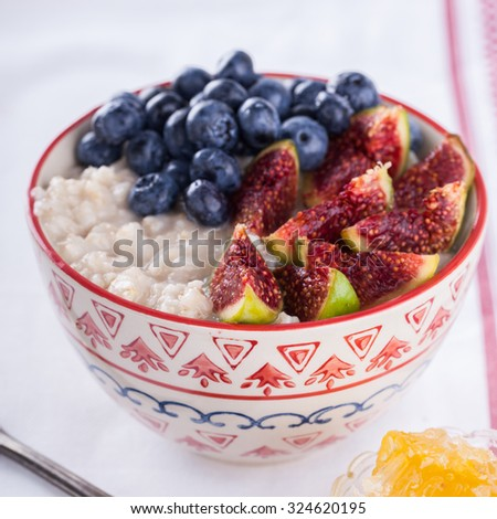 Oatmeal with fig ,blueberries and honey.Healthy Breakfast.selective focus - stock photo