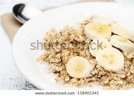 Oatmeal with fresh bananas drizzled with honey over a rustic wooden background. - stock photo