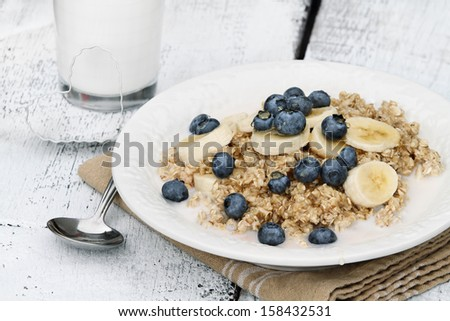 Oatmeal with fresh blueberries and bananas drizzled with honey over a rustic wooden background. - stock photo