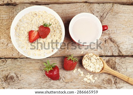 Oatmeal with milk. Porridge with milk. Cereals, delicious Breakfast, diet Breakfast. Ripe strawberries, oatmeal and Cup of coffee latte. Wooden spoon with cereal, a Cup of coffee and bowl of porridge. - stock photo