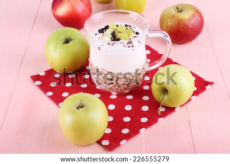 Oatmeal with yogurt in pitcher and apples on napkin on wooden background - stock photo