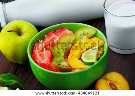 oatmeals in green plate decorated with slice of strawberry,kiwi peach , green apple  with bottle and glass of milk.On dark wooden background.Breakfast. closeup