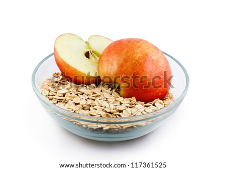 Oats and apple halves in transparent bowl isolated with clipping path - stock photo