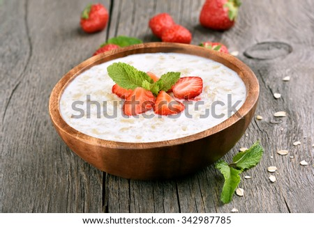 Oats porridge with fresh strawberry in wooden bowl  - stock photo